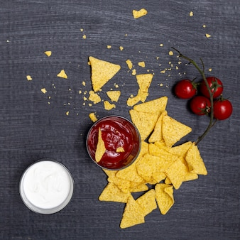 Crumbled nachos with dips and tomatoes