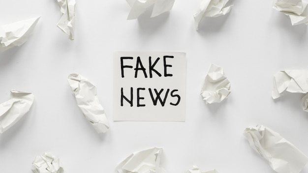 Crumbled paper with fake news message