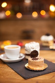 Sbriciolate di cioccolato su un gustoso dessert con biscotto in cima su un tavolo di legno vicino a un delizioso caffè. mini torta al forno secondo la ricetta tradizionale.