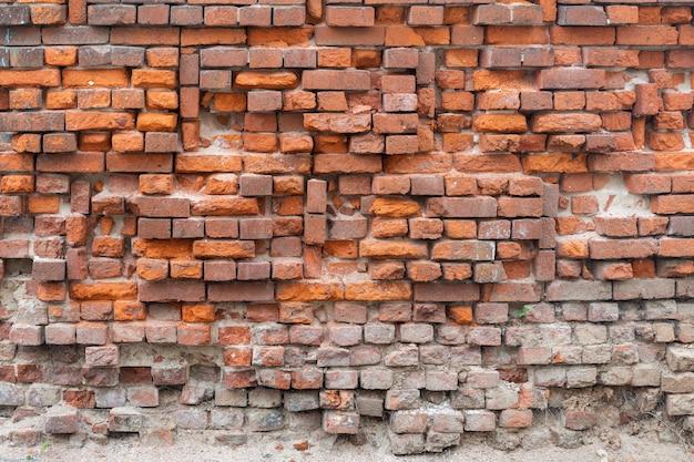 Crumbling red brick wall