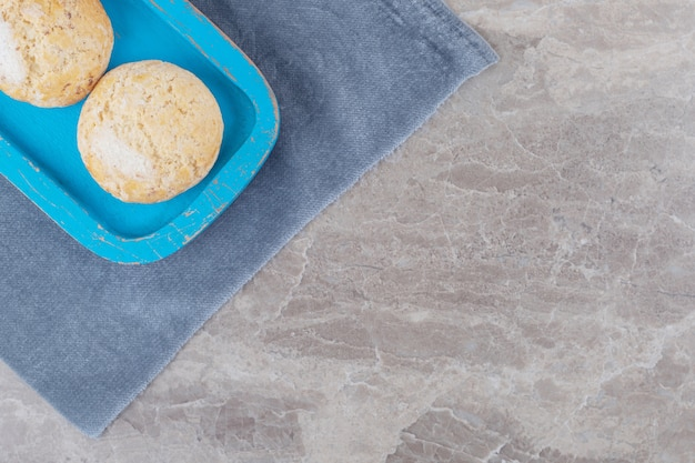 Crumbly cookies on a blue platter on a piece of fabric on marble