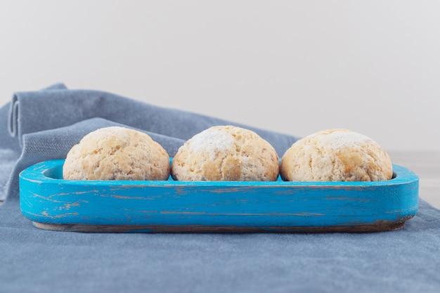 大理石の布の上の青い大皿のもろいクッキー