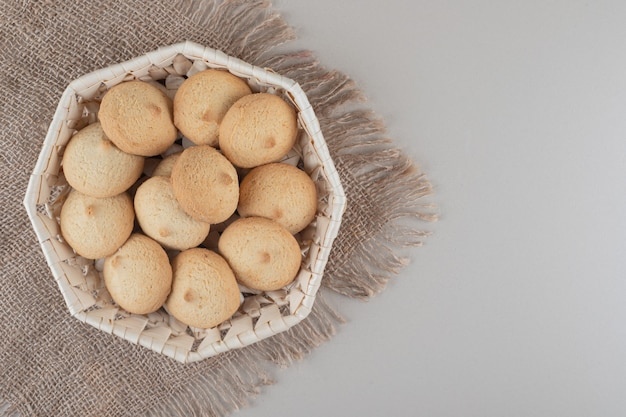 Crumbly cookies in a white basket on a piece of cloth on marble background.
