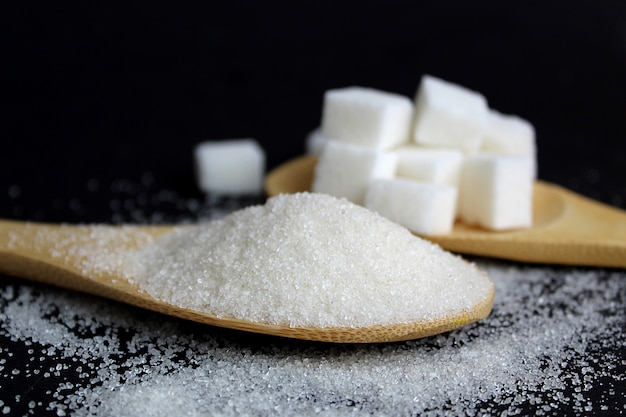 Crumbly and sugar and refined cubes lie on wooden spoons on a black wall. delicious sweet and high-calorie product.