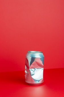 Crumpled aluminum can on a red table. without plastic. environmental pollution. minimalism. design.