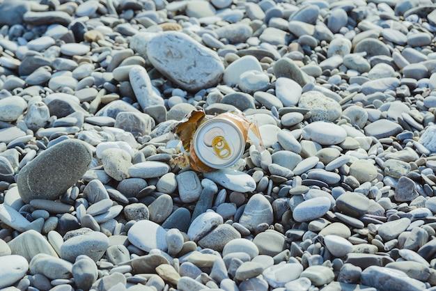 Crumpled aluminum metal orange can on pebble beach, environmental protection concept, horizontal lifestyle stock photo image background