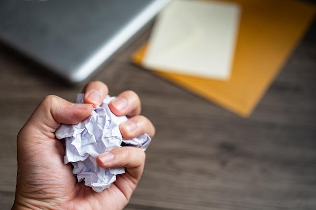 Мятые шары белой бумаги в руке над деревянным столом на рабочем месте