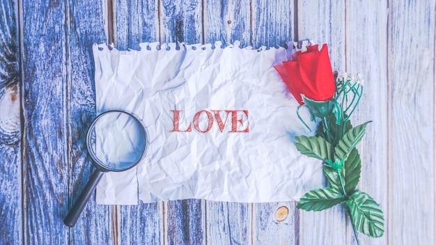 구겨진 된 빈 종이, 빨간 장미와 나무 테이블, 빈티지 종이 평면도에 돋보기. 사랑 또는 발렌타인 데이 개념.