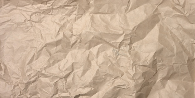 Crumpled blank sheet of brown wrapping kraft paper, vintage texture for the designer, full frame, banner