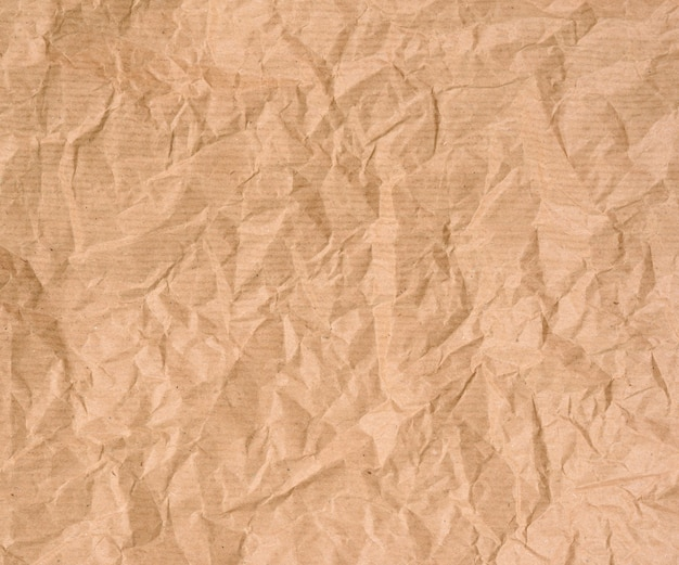 Crumpled blank sheet of brown wrapping kraft paper, vintage texture for the designer, full frame