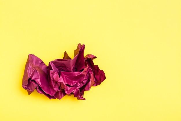 黄色の背景に色の紫紙のしわくちゃの空白のシート。上面図。コピースペース