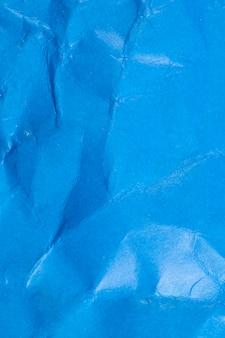 しわくちゃの青い紙の背景。