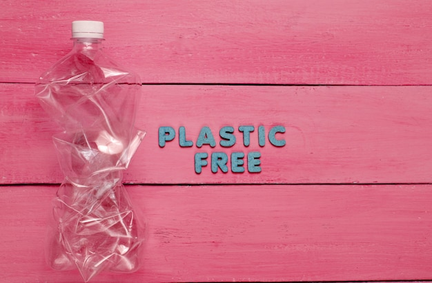 Crumpled bottle on red wooden surface with text plastic free
