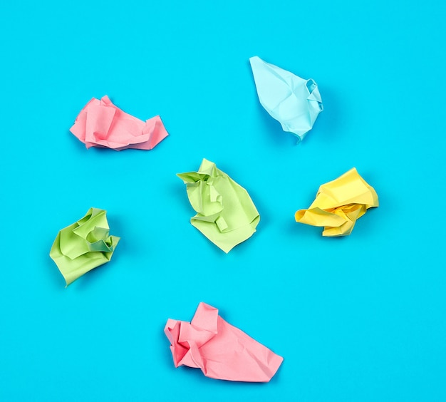 Crumpled bright multi-colored paper on a blue background