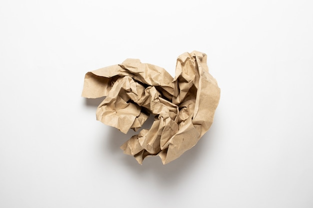 Crumpled brown craft paper on a white background.