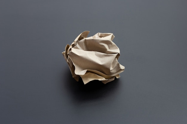 Crumpled brown paper ball on dark surface. copy space