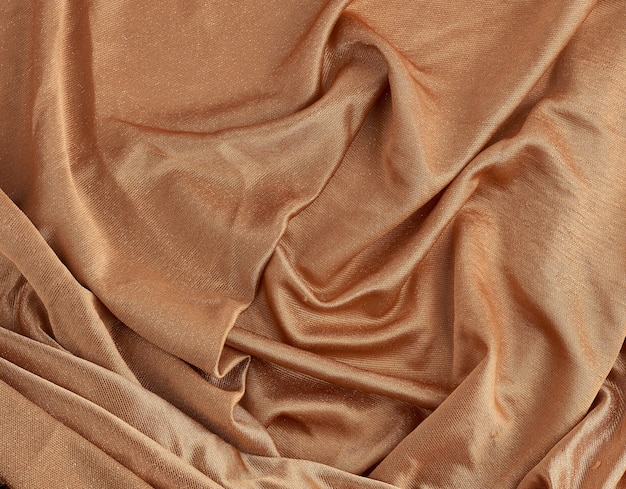 Crumpled brown shiny fabric for dress making, satin