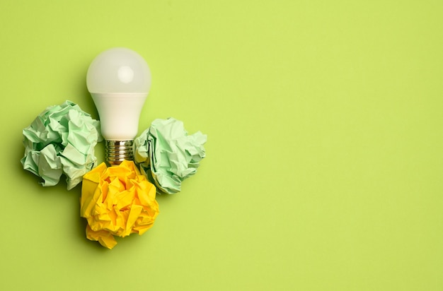 Crumpled colored balls of paper and glass white lamp on green surface, top view