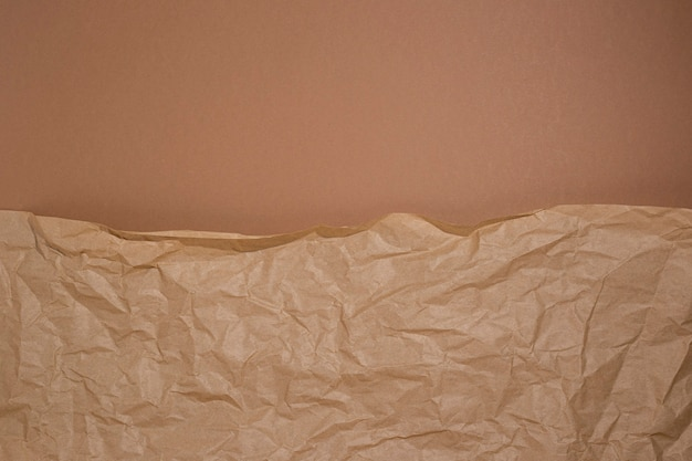 Crumpled craft paper on a brown cardboard background.