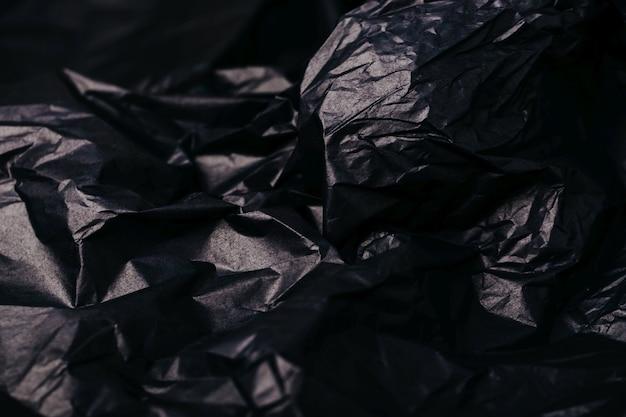 Мятой темно-черной бумаги текстуры абстрактный фон