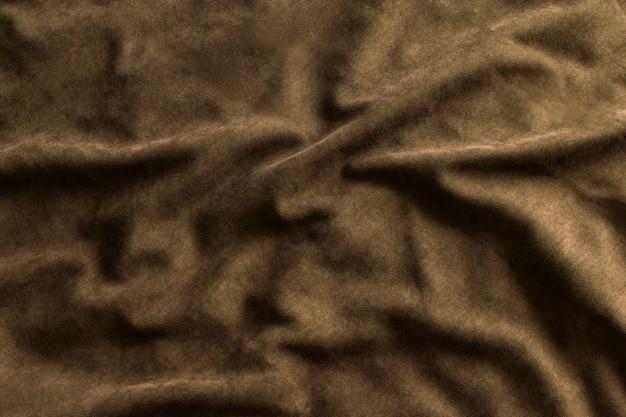 波とひだの背景とテクスチャーを備えたダークブラウンの色合いのしわくちゃの緻密な生地。上面図。