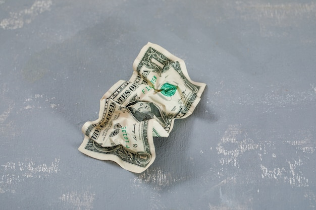 Crumpled dollar banknote on plaster table .