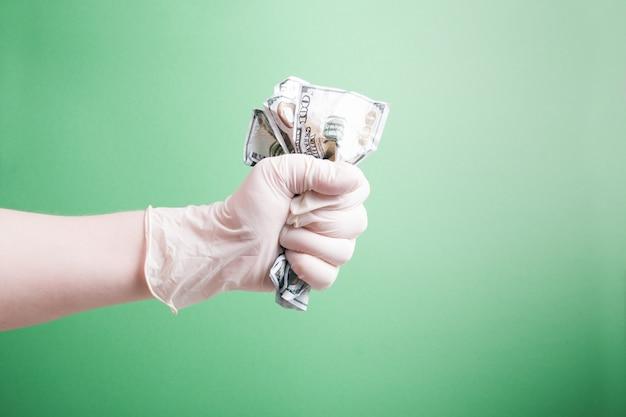 고무 장갑 녹색 배경에 구겨진 된 달러 지폐 손 손