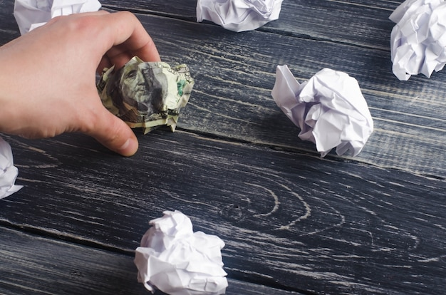 A crumpled dollar on a table next to white paper balls
