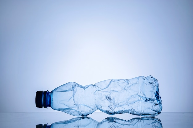Crumpled empty clear plastic bottle on blue