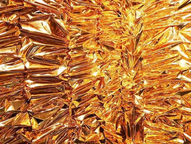 Скомканная предпосылка текстуры бумаги сусального золота.
