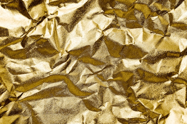 Crumpled gold paper textured background