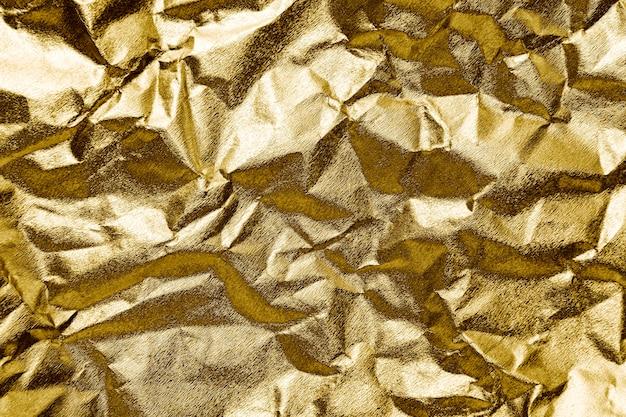 しわくちゃの金の紙の織り目加工の背景