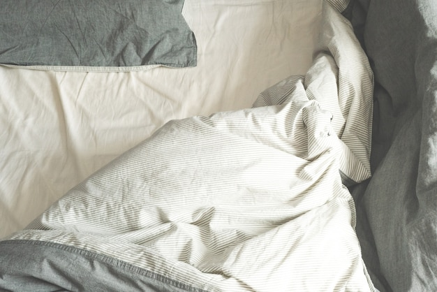 Crumpled gray fabric. bed in the morning. the spread out bed. linens.