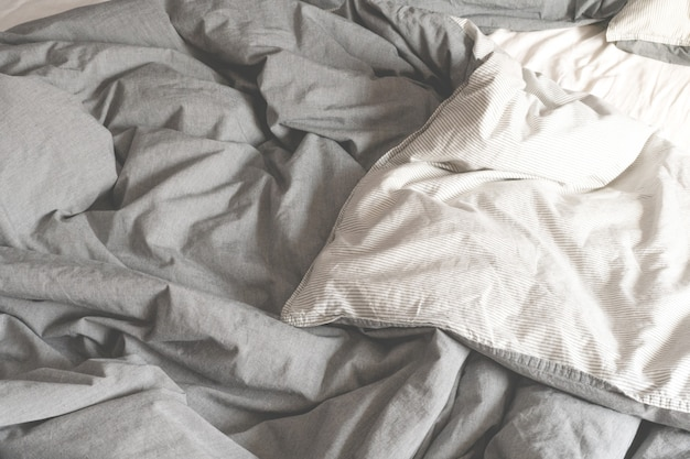 Crumpled gray fabric. bed in morning. the spread out bed.