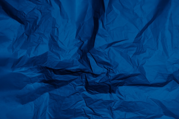 Crumpled gray paper texture, classic blue background