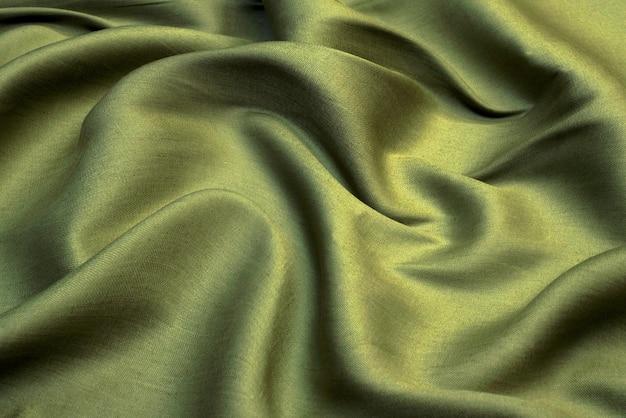 Текстура мятой зеленой ткани, волнистая морщинистая ткань. мягкий фон льняной ткани.