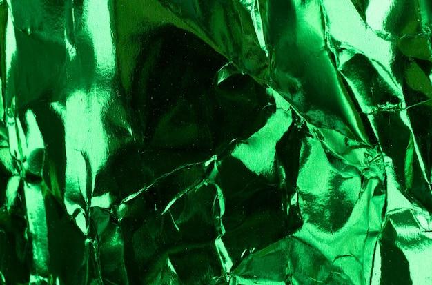 Crumpled green foil paper texture.