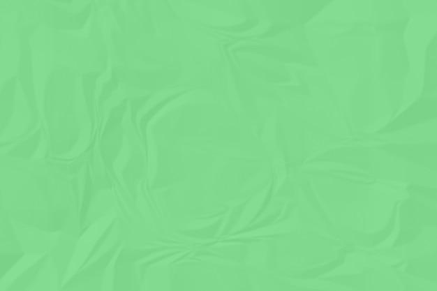 しわくちゃの緑の紙の背景をクローズアップ