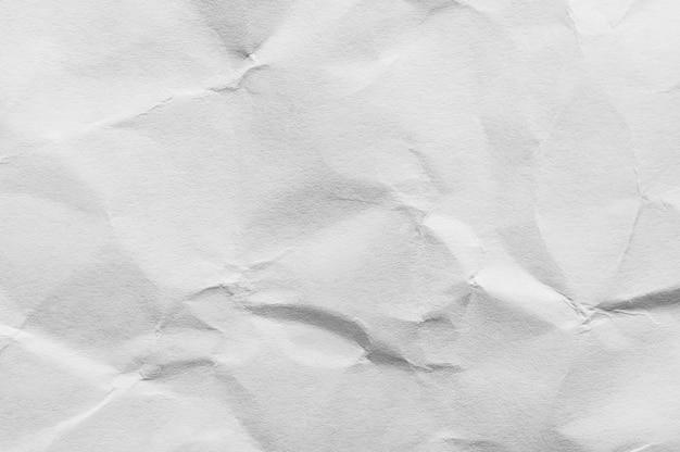 しわくちゃの軽いクラフト紙の背景。破損したシートの白い表面にコピースペースがあります。テキストやクリエイティブなデザインのための空白の場所。圧搾された表面の概念のテンプレート。