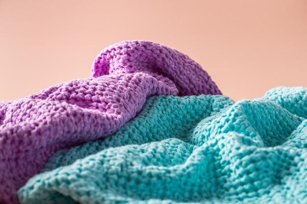 Мятые льняные и хлопковые банные и спа-полотенца, свернутые в рулон на розовом