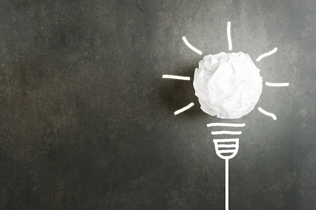 Crumpled lump of white paper like a light bulb white glow with illustration