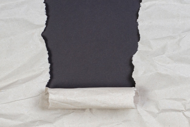 Crumpled package paper torn to reveal black wall with copy space