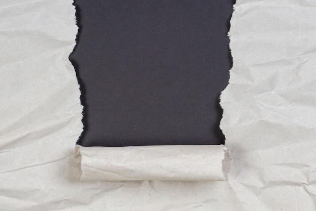 しわくちゃのパッケージ紙が破れ、コピースペースのある黒い壁が見える