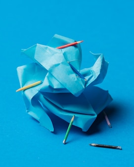 파란색 배경에 구겨진 종이와 연필