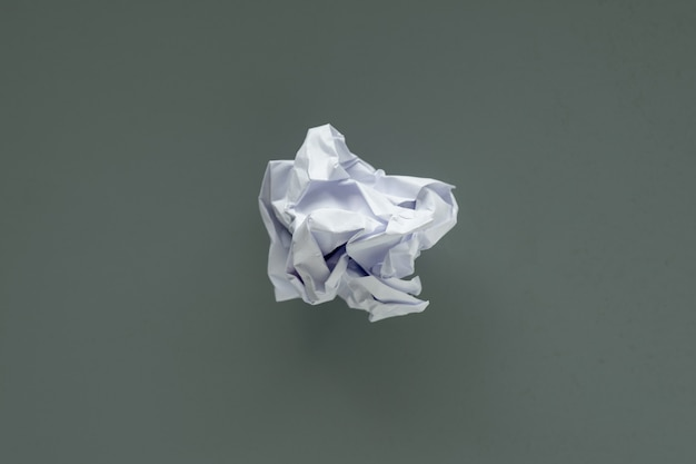 Crumpled paper ball on gray background