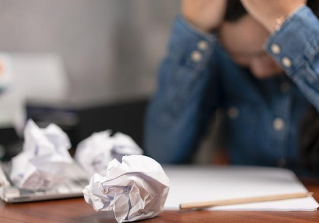ビジネスマンとのしわくちゃの紙のボールは問題を抱えています
