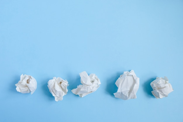 Crumpled paper balls on blue. concept idea and creative