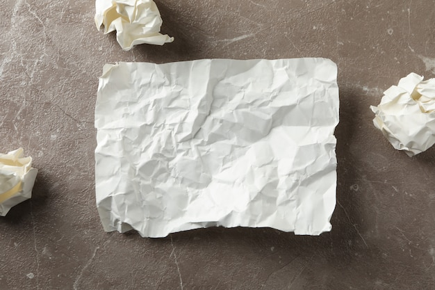 Crumpled paper and balls on grey background, top view