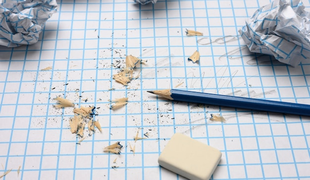 Crumpled paper balls and a sharpened wooden pencil with shavings on a checkered paper sheet, close up