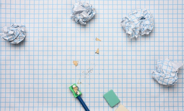 Crumpled paper balls and a sharpened wooden pencil with shavings on a checkered paper sheet